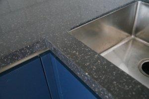 Кухня синего цвета в современном стиле Fenix Фасады верх: акрила SENOSAN Ваниль 7496 TopMatt (S-LINE cream a04 крем) Фасады низ: Fenix 0754 Blu Fes Столешница: Акриловый Искуственный камень Staron Mosaic qn287 nimbus Фурнитура: Скрытые ручки-профиль Schuco, петли и выдвижные ящики BLUM, сушка для посуды SIGE/нержавеющая сталь Корпус: ЛДСП, цвет Кремовый 7031 LED подсветка с датчиком движения